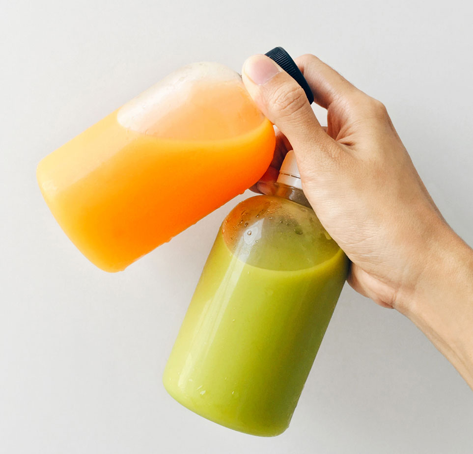 Individual holding two freshly pressed organic juices in water bottles